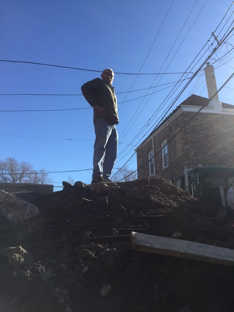man standing on rubble pile