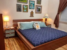 Chickadee room features hardwood floors, two nightstands, a dresser, and a king bed with blue sheets and pillows. Walls have art. There is a window to the left of the bed.