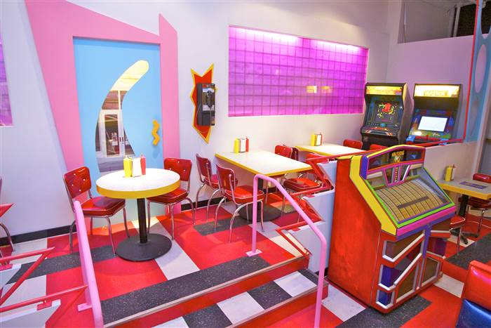 colorful room with tables, chairs, jukebox
